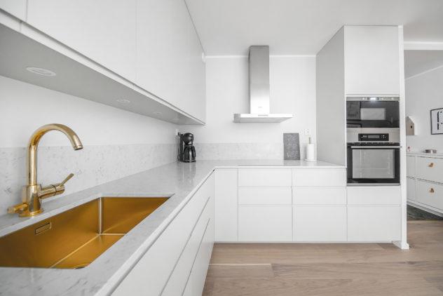 Keittiö, sileä ovi, jyrsitty vedinura, Noble Carrara kivitaso altapäin kiinitetyllä altaalla. Väri: valkoinen puolimatta.