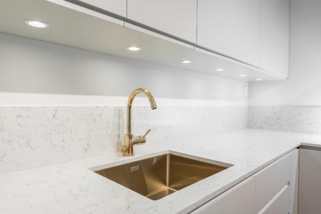 Keittiö, sileä ovi, jyrsitty vedinura, Noble Carrara kivitaso altapäin kiinitetyllä altaalla. Väri: valkoinen puolimatta